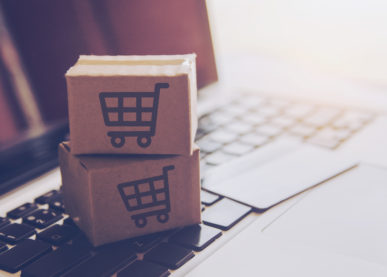 Shopping online concept - Shopping service on The online web. with payment by credit card and offers home delivery. parcel or Paper cartons with a shopping cart logo on a laptop keyboard